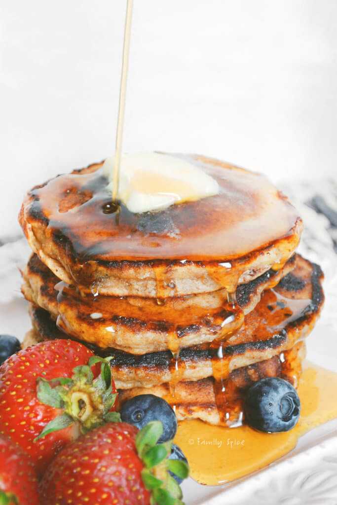 A stack of pancakes with syrup poured on it