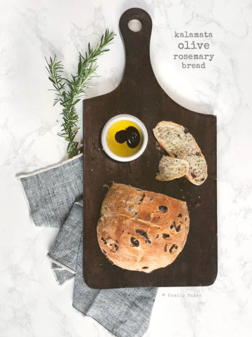 A ball of rosemary olive bread on a dark wood cutting board sliced with a small bowl of olive oil and vinegar by FamilySpice.com