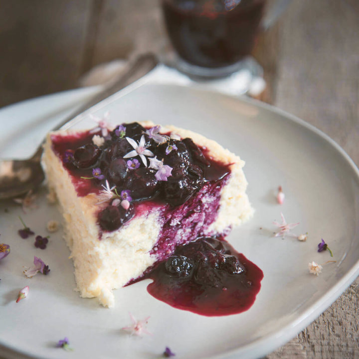 A slice of low carb cheesecake with blueberry sauce over it