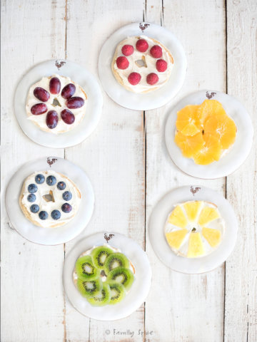 Six bagels each topped with fruit: raspberries, grapes, blueberries, kiwi, pineapple and oranges