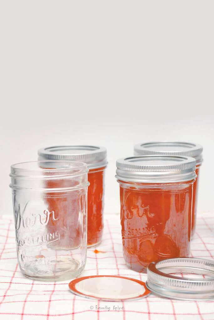 An empty mason jar along with peach jam filled mason jars