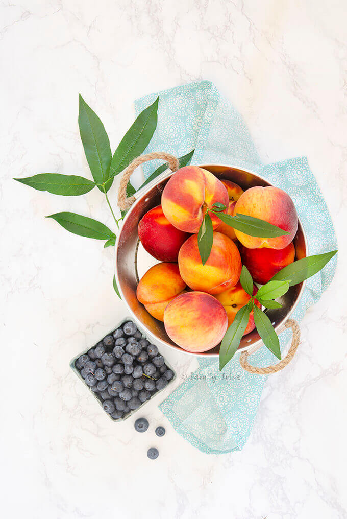 A bowl full of fresh peaches with a carton of fresh blueberries by FamilySpice.com