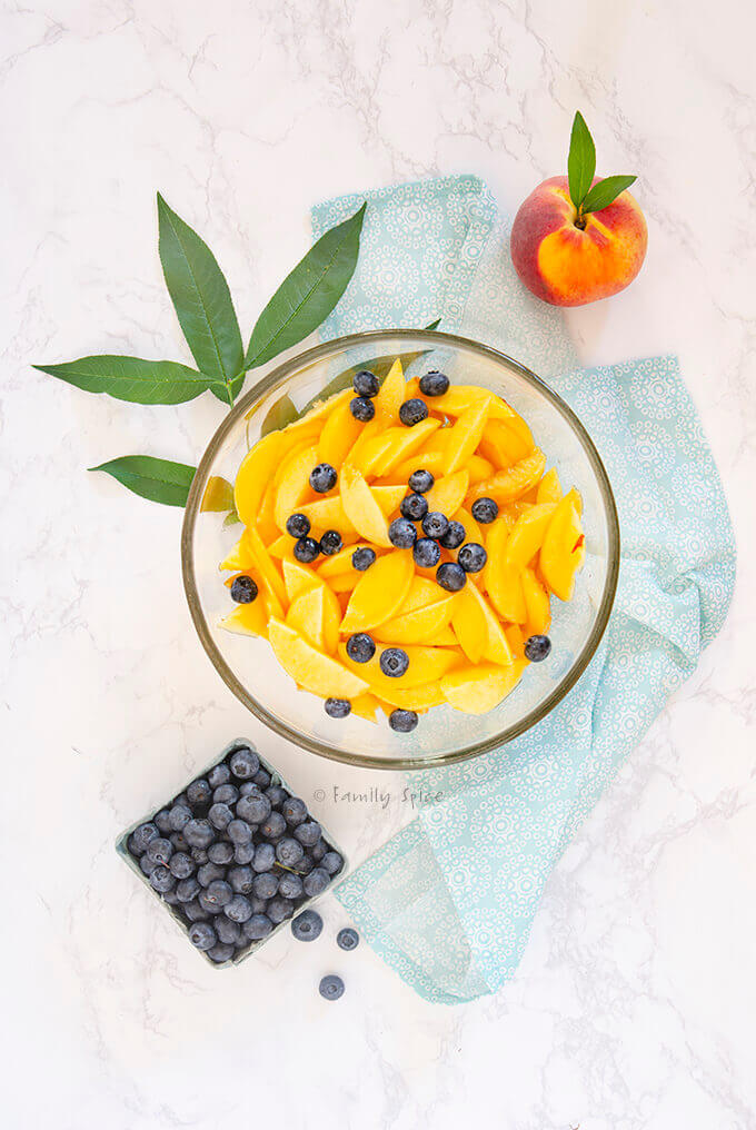 A bowl of sliced peaches and blueberries to make cobbler by FamilySpice.com