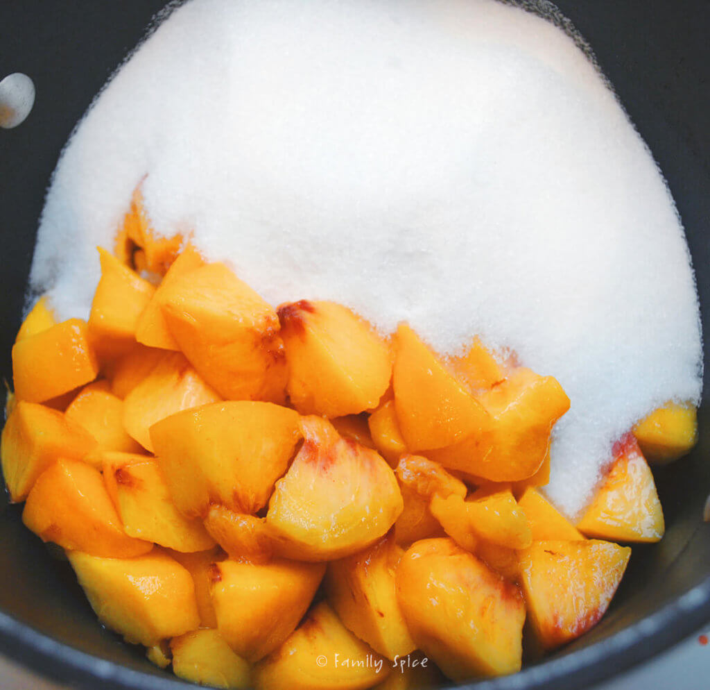 Chopped peaches in a pot with sugar