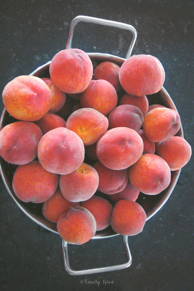 Top view of a colander full of fresh peaches by FamilySpice.com