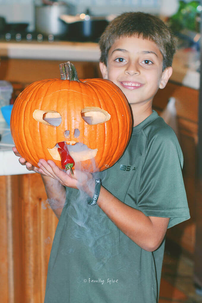 "Boy holding a ""smoking"" carved pumpkin with a chili pepper by FamilySpice.com"