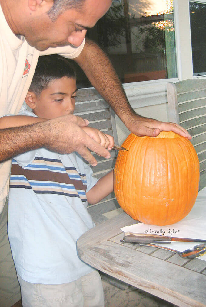 My boy carving a pumpkin with his dad's help by FamilySpice.com