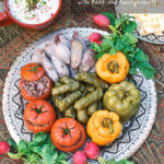 Overhead shot of a platter full of Persian dolma (or dolmeh/dolmades), stuffed grape leaves, tomatoes, onions and peppers with a bowl of yogurt dip - FamilySpice.com