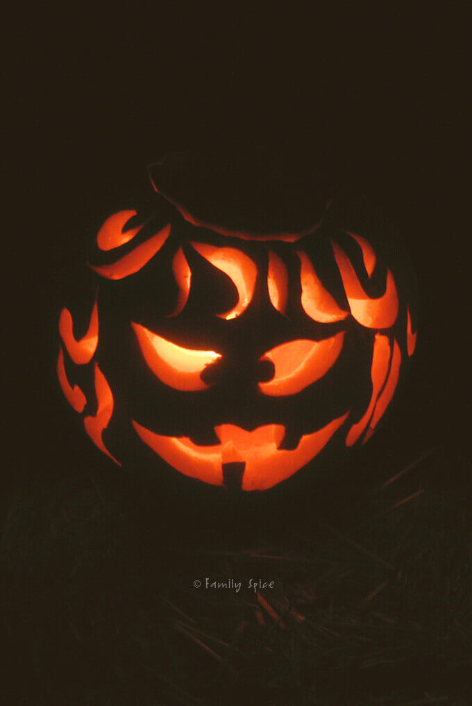A carved pumpkin glowing in the dark by Familyspice.com