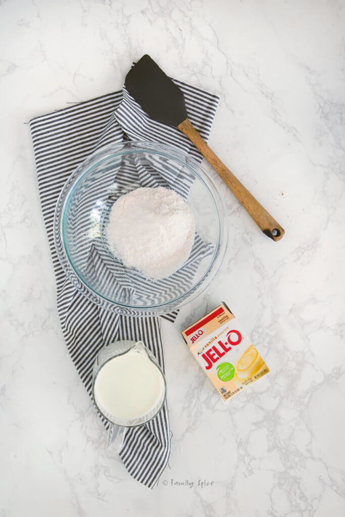Jello pudding box next to a boil with pudding powder and a measuring cup filled with milk