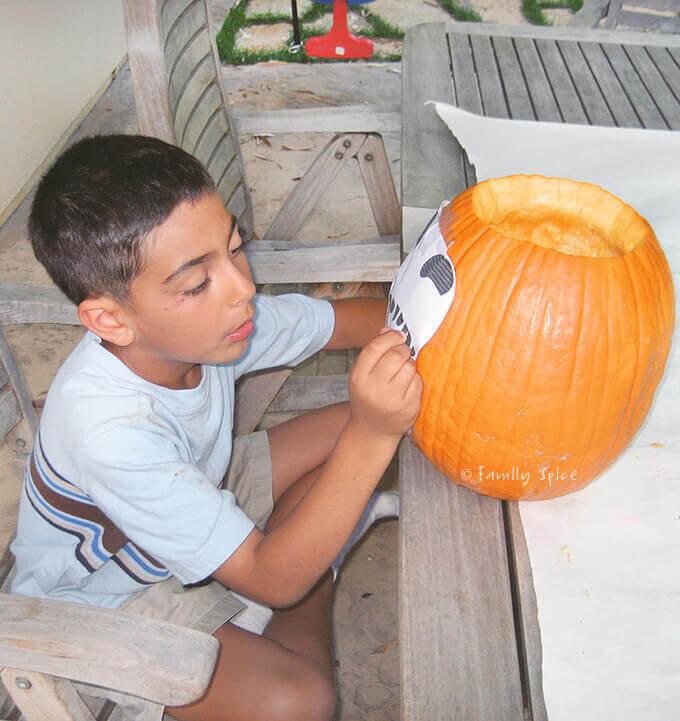 My boy outlining a stencil on his pumpkin by FamilySpice.com