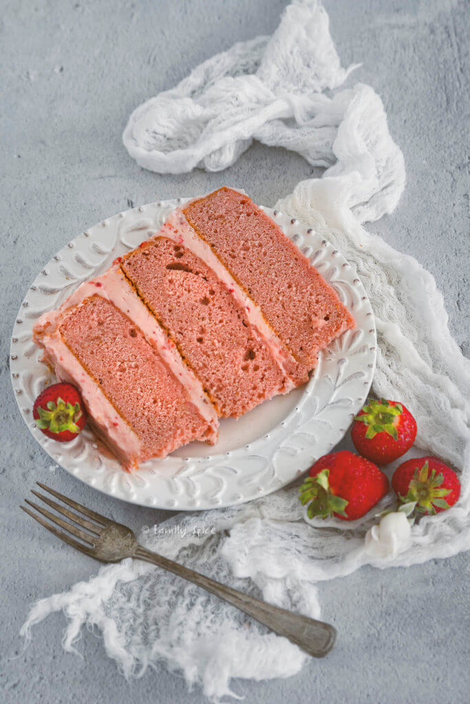 A slice of 3 layered strawberry cake with strawberry frosting on a white plate with fresh strawberries