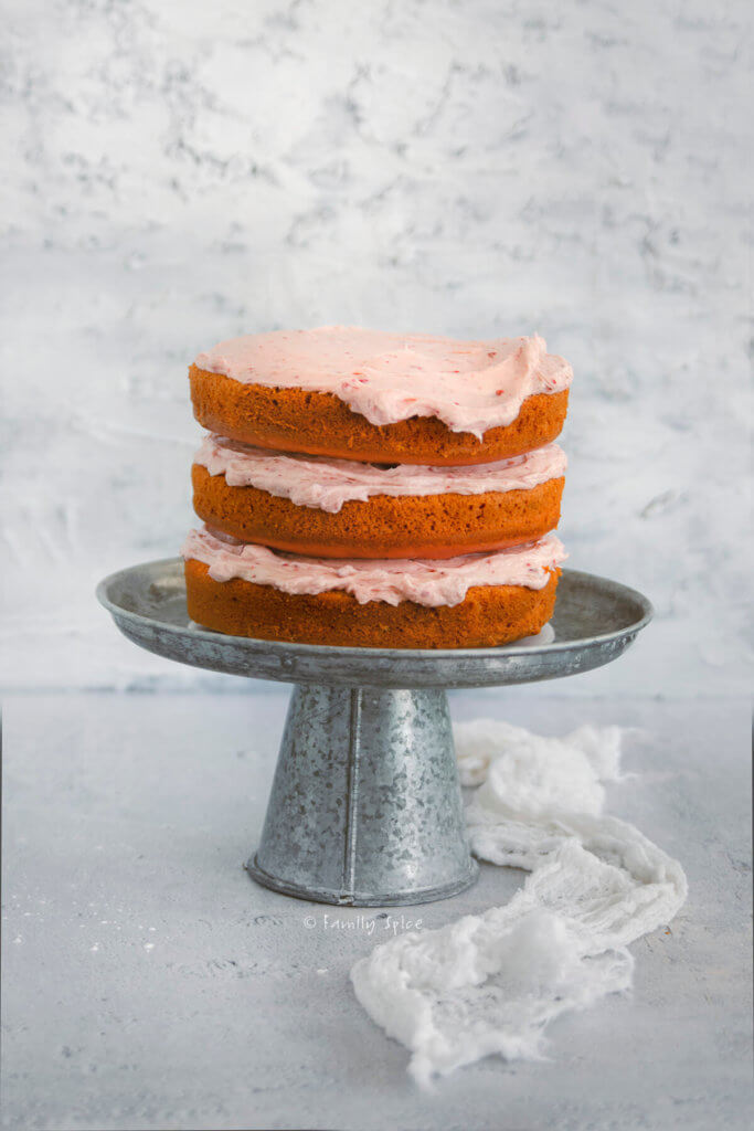Three tiered strawberry cake with strawberry frosting in between layers on a metal cake stand