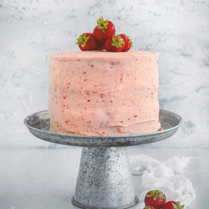 Side view of a 3 layered strawberry cake with strawberry frosting and topped with fresh strawberries on a rustic metal cake stand