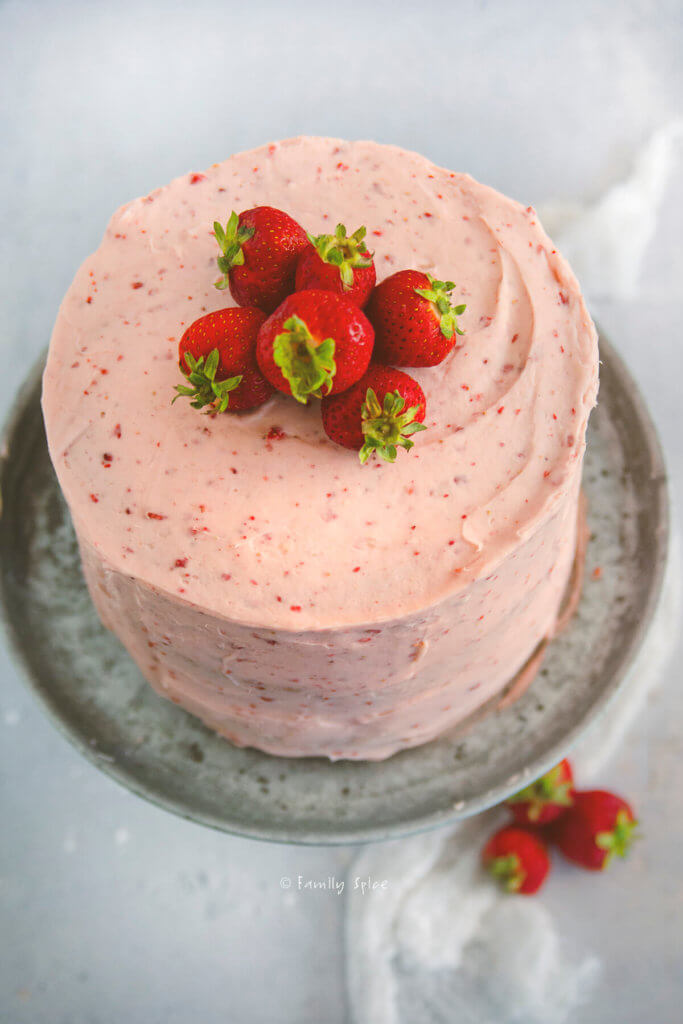 Top of a 3 layered strawberry cake with strawberry frosting and topped with fresh strawberries