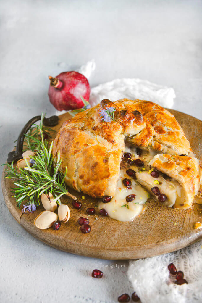 Baked brie wrapped in puff pastry and stuffed with pomegranate and nuts cut open on a round wooden tray