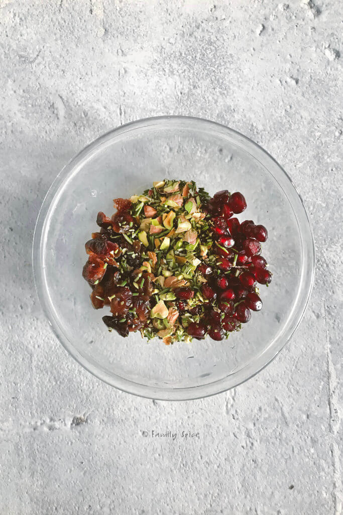 A small glass bowl with chopped pistachios, dried cranberries, pomegranate arils and chopped rosemary in it