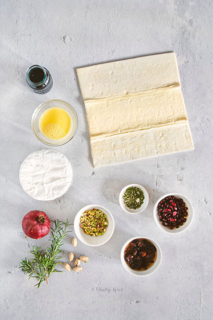 A sheet of raw puff pastry on a concrete work surface with other ingredients around it to make stuffed baked brie