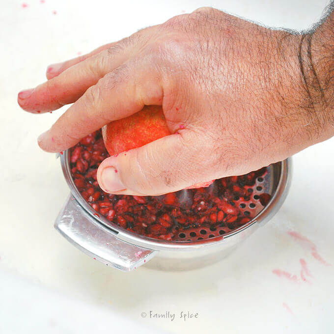 Juicing pomegranate seeds with a hand juicer by FamilySpice.com