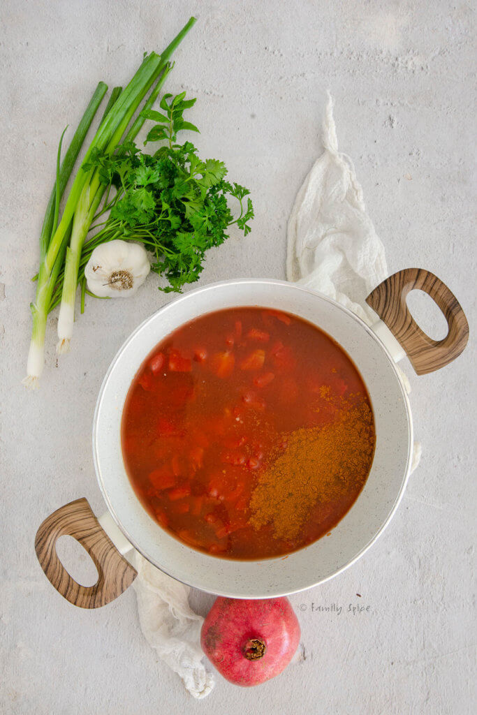 A white pot with ingredients to make tomato pomegranate sauce in it