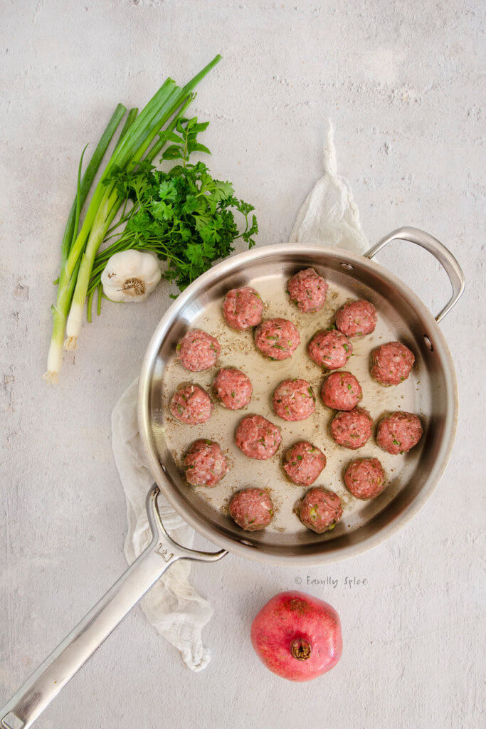 Browning lamb meatballs in a stainless frying pan with fresh herbs and garlic next to it