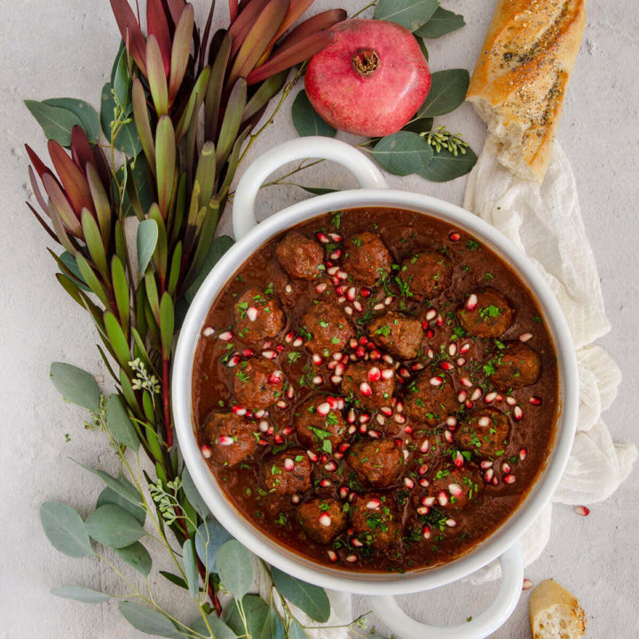 A white serving bowl with lamb meatballs in tomato pomegranate sauce with greenery and baguette around it
