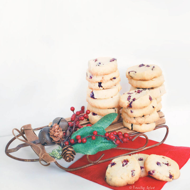 Slices of cherry orange cookies on a mini sleigh and red napkin