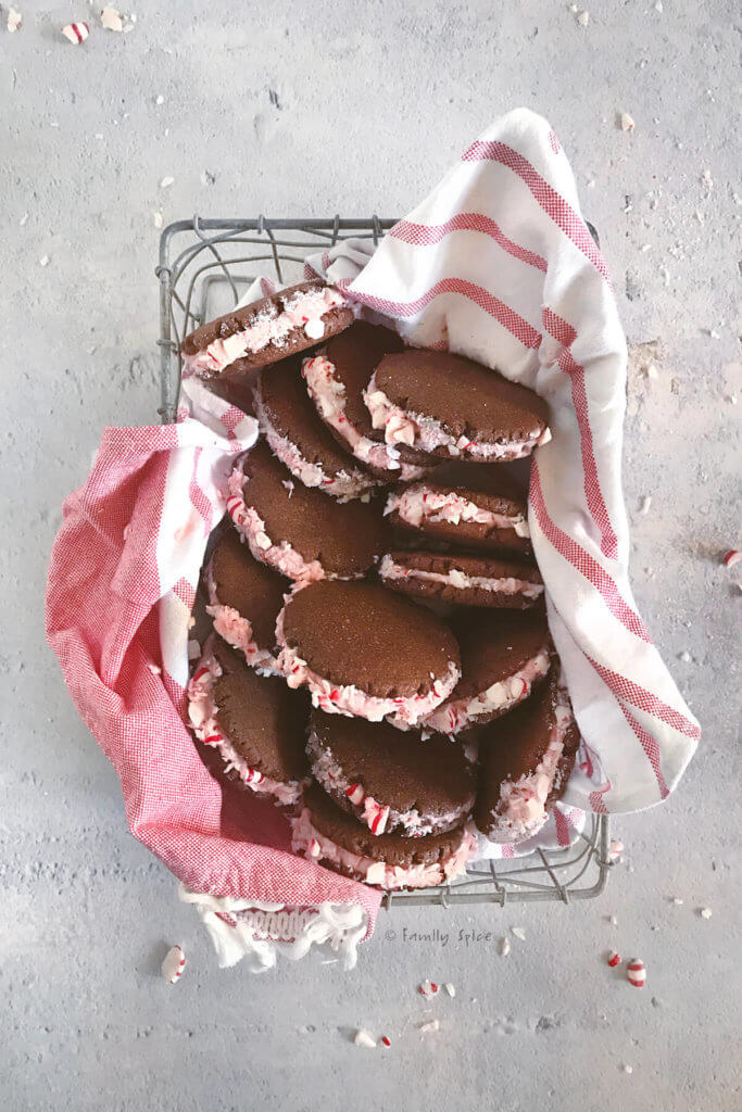 A wire basket lined with tea towel filled with chocolate sandwich cookies with peppermint frosting