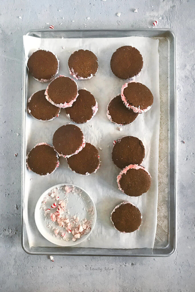 A baking sheet filled with peppermint chocolate sandwich cookies with a plate of crushed peppermints