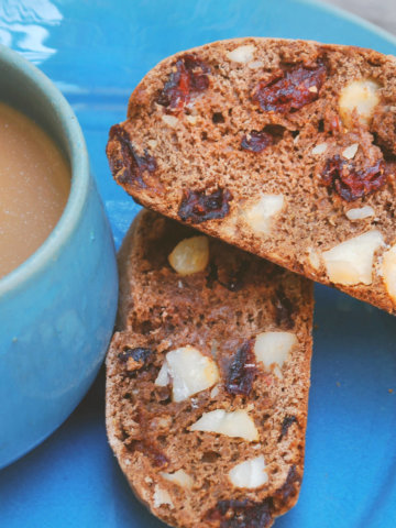 Chocolate biscotti slices on a blue plate with a blue mug of coffee