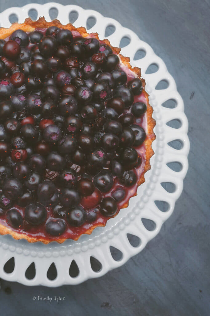 Top view of a blueberry tart on a white serving dish