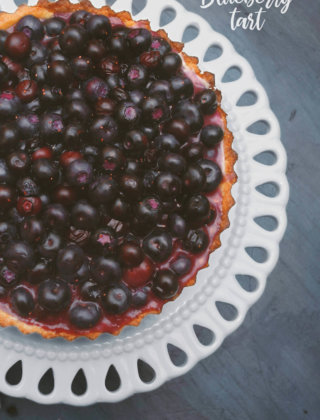 Overhead shot of a blueberry tart on a white cake pedestal by FamilySpice.com