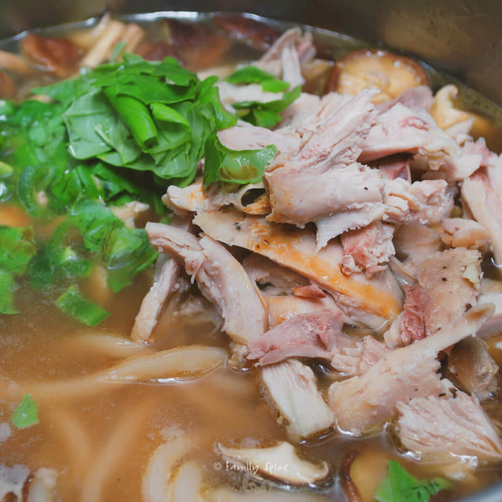 Adding fresh herbs and shredded chicken to soup