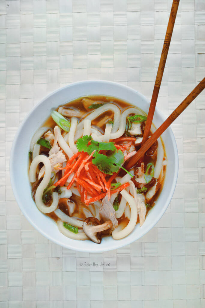 Top view of a bowl of chicken udon soup with chopsticks in it