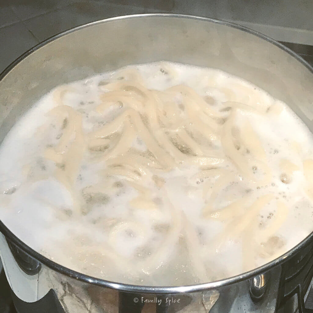Udon noodles boiling in a pot of hot water