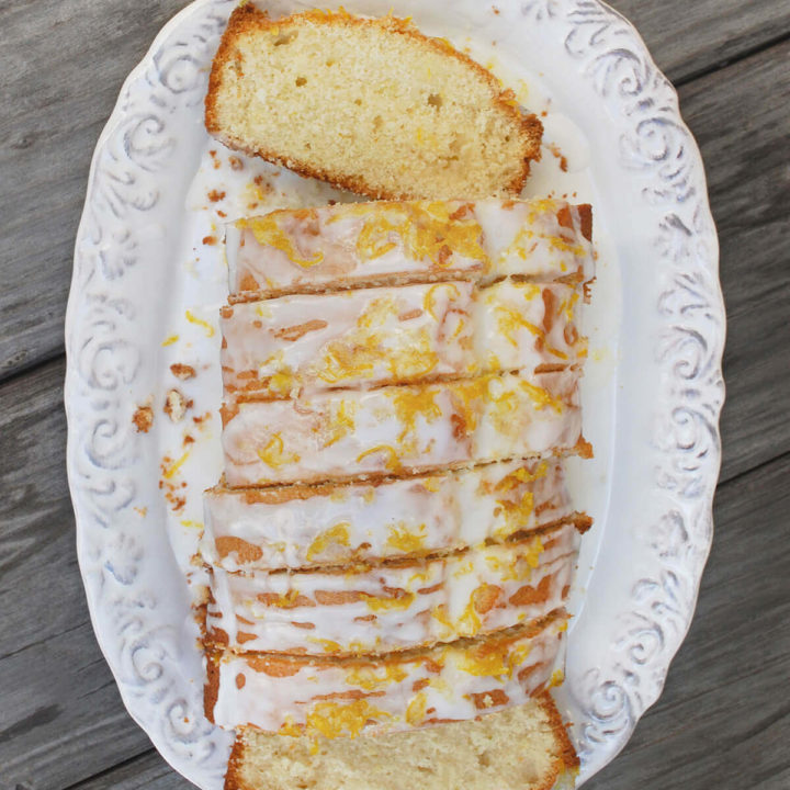 Top view of a loaf of lemon tea cake cut into slices onto a white oval platter