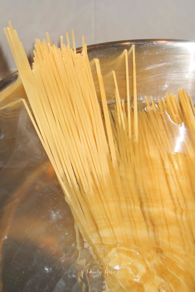 Dry spaghetti added to a pot of boiling water