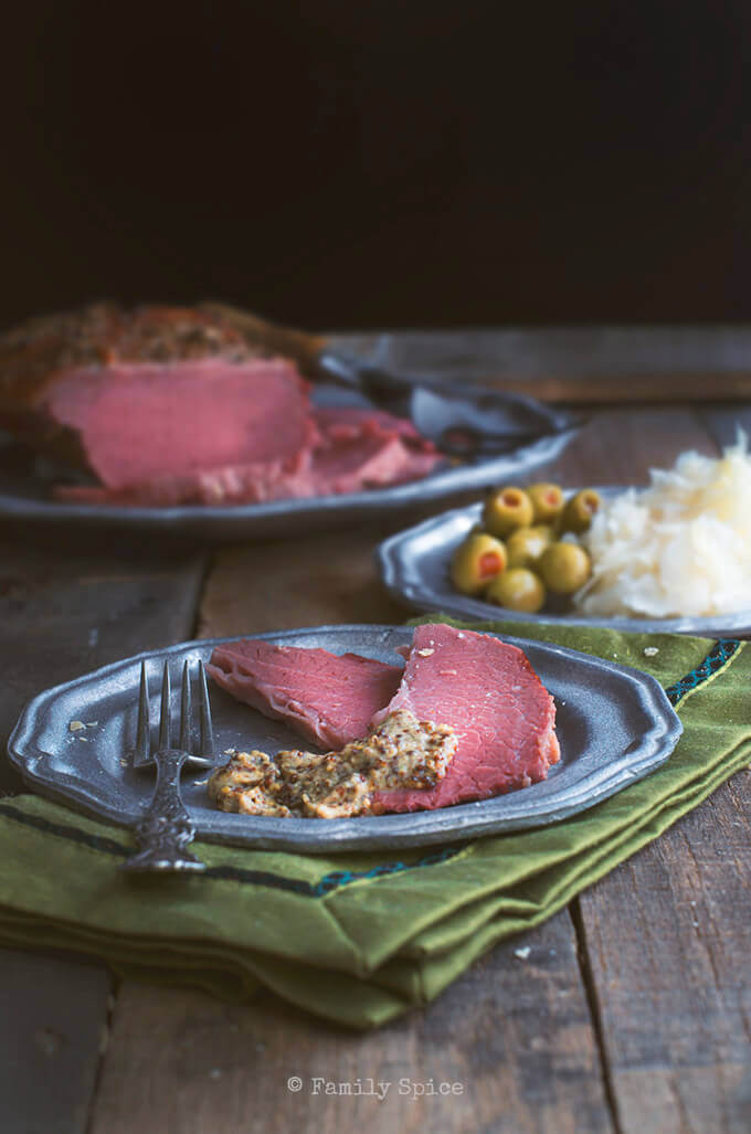 Baked corned beef on pewter plate with a dark rustic background by FamilySpice.com