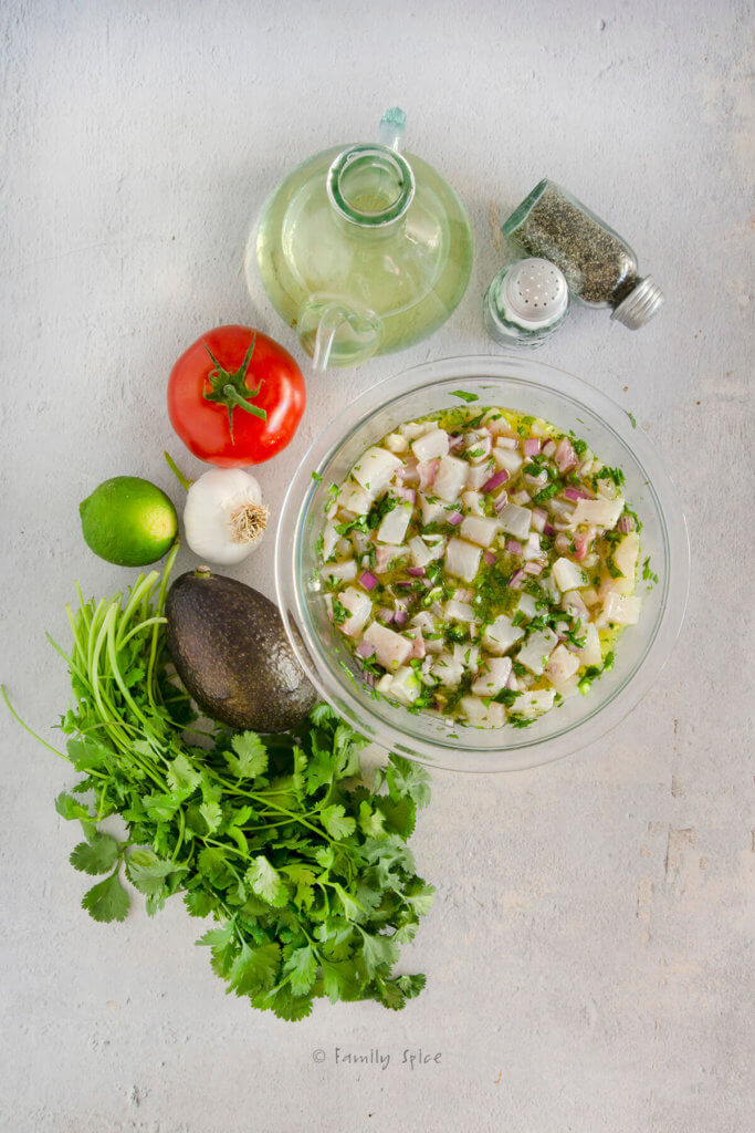 Top view of a glass mixing bowl with chopped ingredients mixed together to make Mexican ceviche