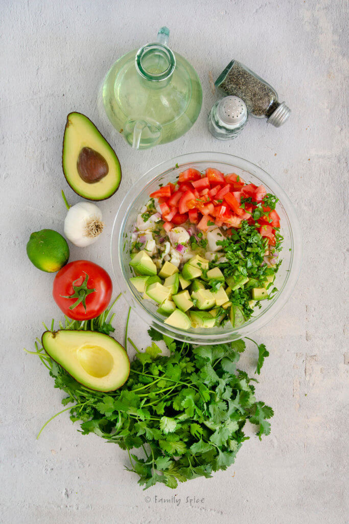 Top view of a glass mixing bowl with chopped tomatoes, avocado and cilantro added to fish mixture to make Mexican ceviche