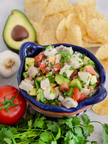 Mexican ceviche in a blue terracotta bowl with tortilla chips and ingredients around it