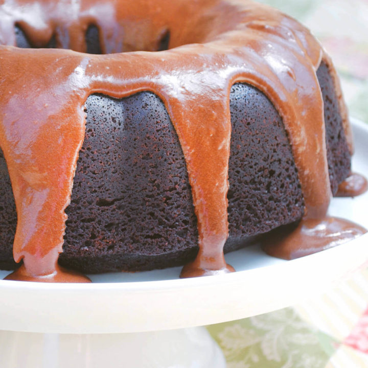 A root beer bundt cake with root beer frosting dripping down on it