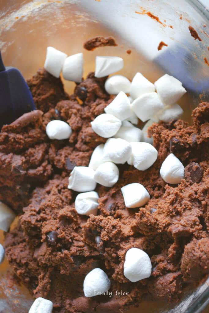Adding mini marshmallows to chocolate cookie batter