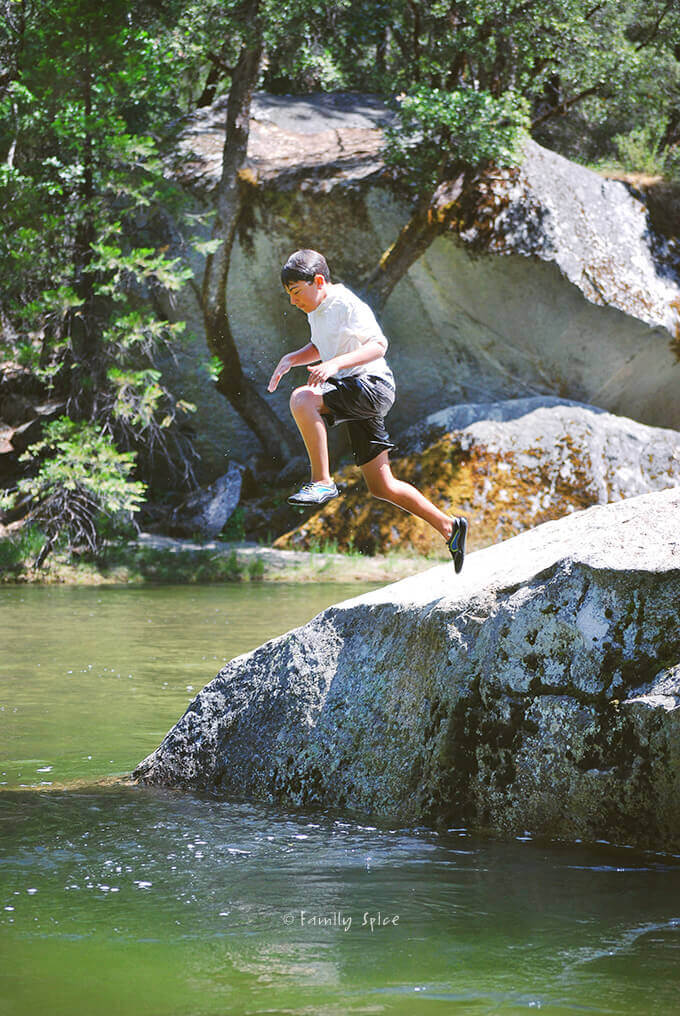My boy jumping off a rock into lake in Yosemite Valley by FamilySpice.com
