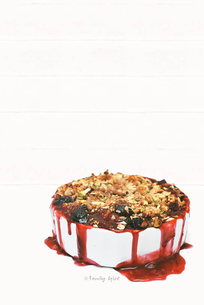 A small individual sized strawberry rhubarb crisp dripping with juice by FamilySpice.com