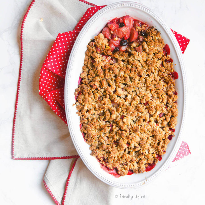 Top view of a baked strawberry rhubarb crisp with the topping removed over a small part of it