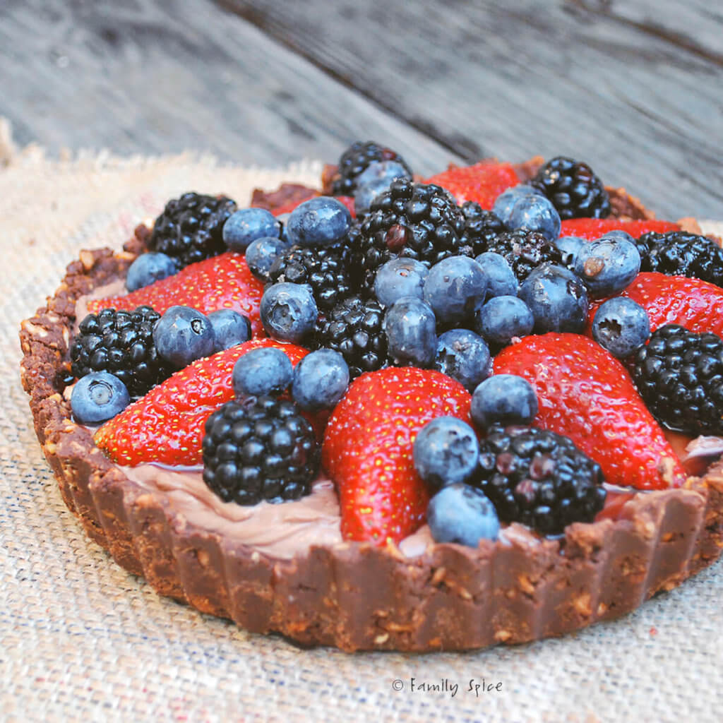 Side view of a Nutella pie with a variety of berries on top