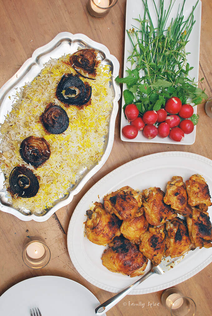 Overhead shot of a Persian meal: basmati rice with onion crust, saffron chicken, radishes and fresh herbs by FamilySpice.com