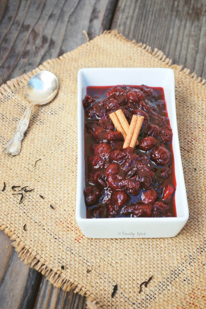 A rectangular dish with spiced tea cranberry sauce and cinnamon sticks on top of it