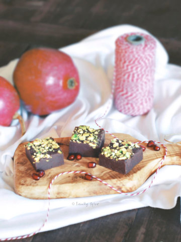 3 pieces of pomegranate fudge topped with pistachios with pomegranates behind it